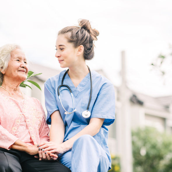 Smiling nurse caregiver holding hand of happy Asian elderly woman outdoor in the park